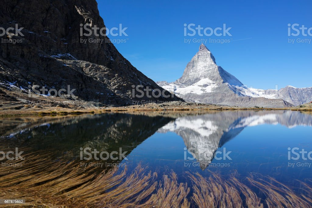 Matterhorn with reflection in lake with clear blue sky stock photo