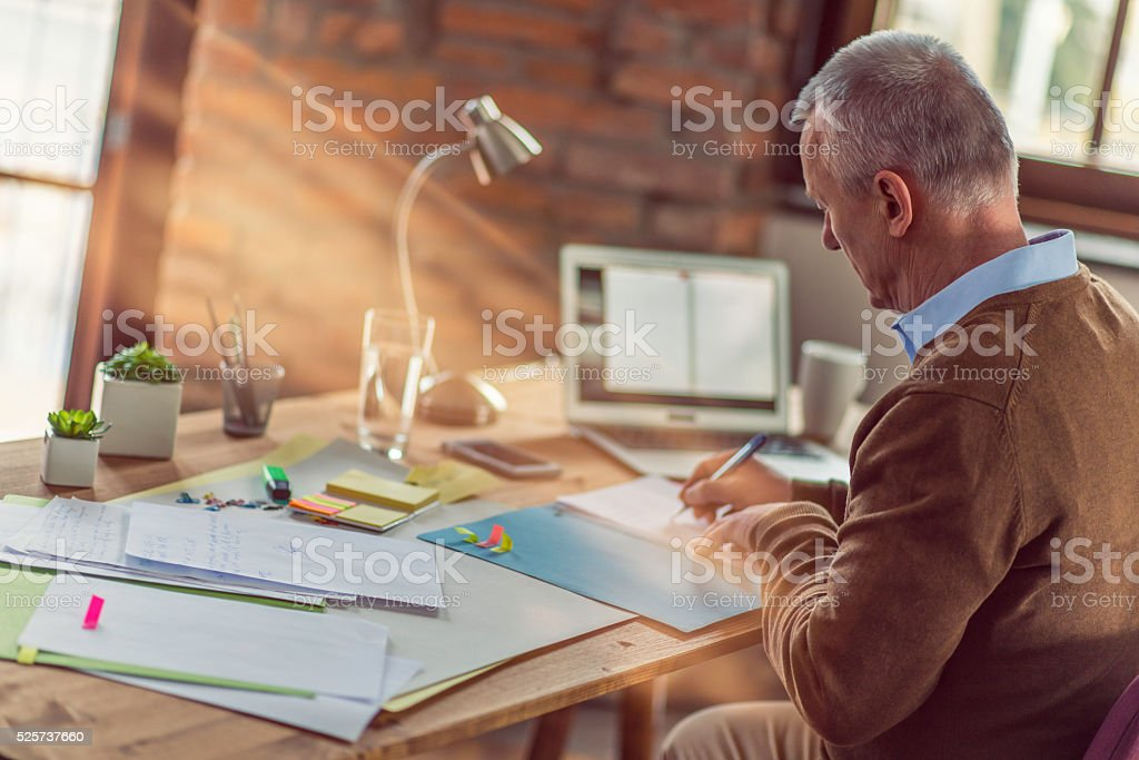Mature accountant in the office reviewing notes stock photo