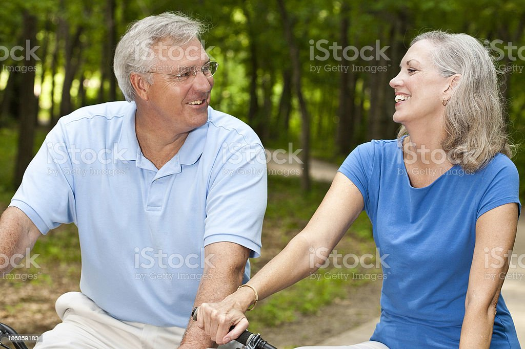 Mature Adult Bikers Laughing Together on Bikes royalty-free stock photo
