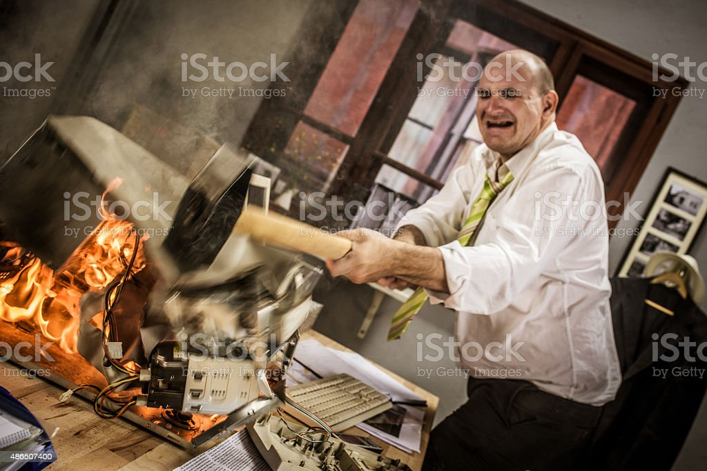 Mature adult businessman smashing computer on fire with hammer stock photo