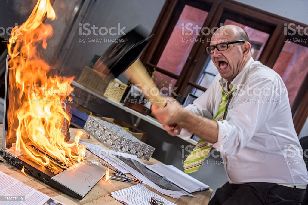 Mature adult businessman smashing laptop on fire with hammer stock photo