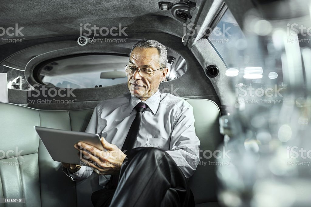 Mature adult businessman working on digital tablet in limousine. stock photo