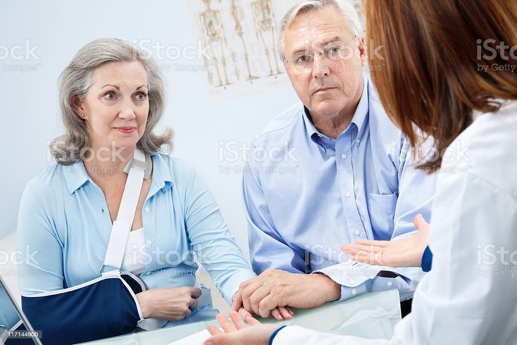 Mature Adult Couple Having Serious Conversation With Doctor royalty-free stock photo