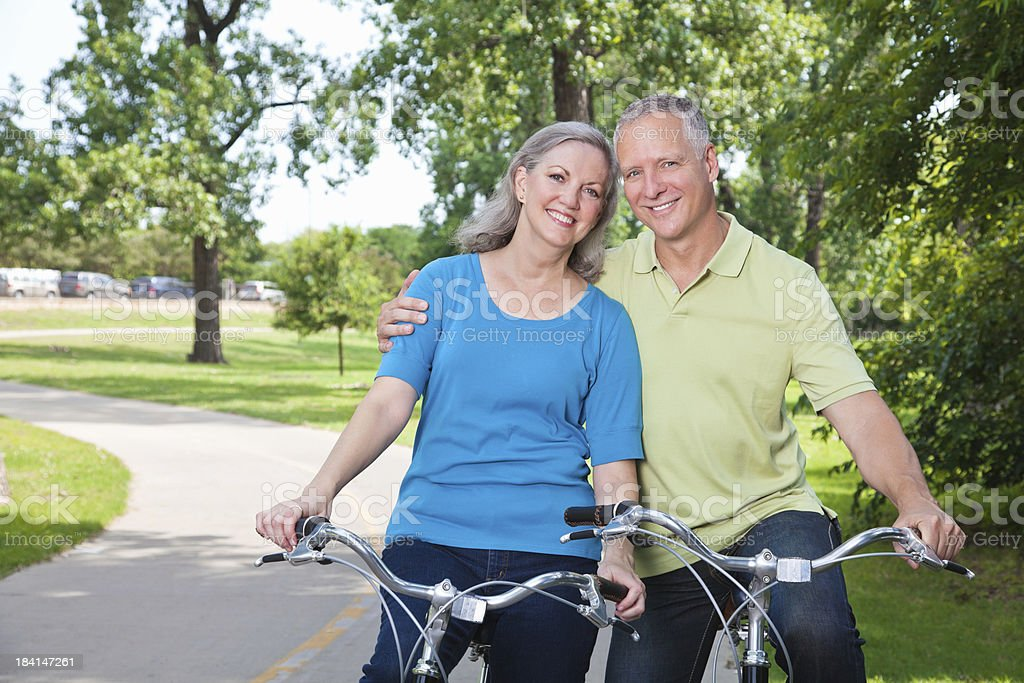 Mature Adult Couple Hugging While on Bikes at a Park royalty-free stock photo