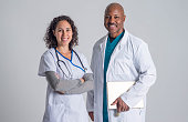 Mature adult male doctor working with young attractive female nurse