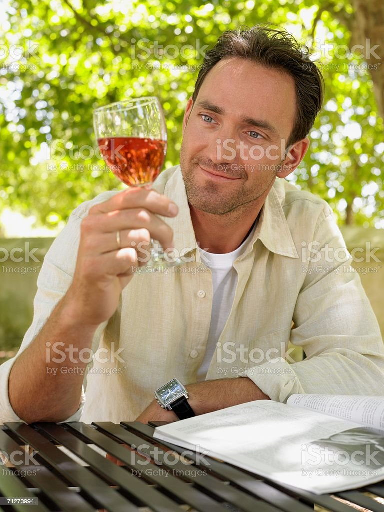 Mature adult man admiring a glass of wine stock photo