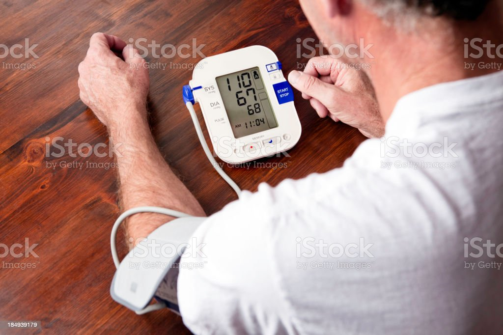 Mature adult man checking blood pressure stock photo