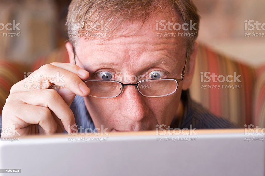 Mature adult raises his eyes over discovery on laptop screen stock photo