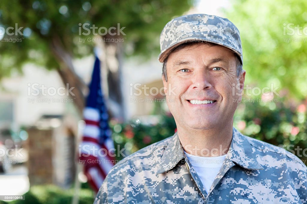 Mature adult soldier in uniform smiling outdoors stock photo