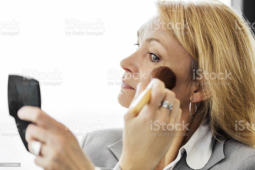 Mature adult woman applying blush. royalty-free stock photo