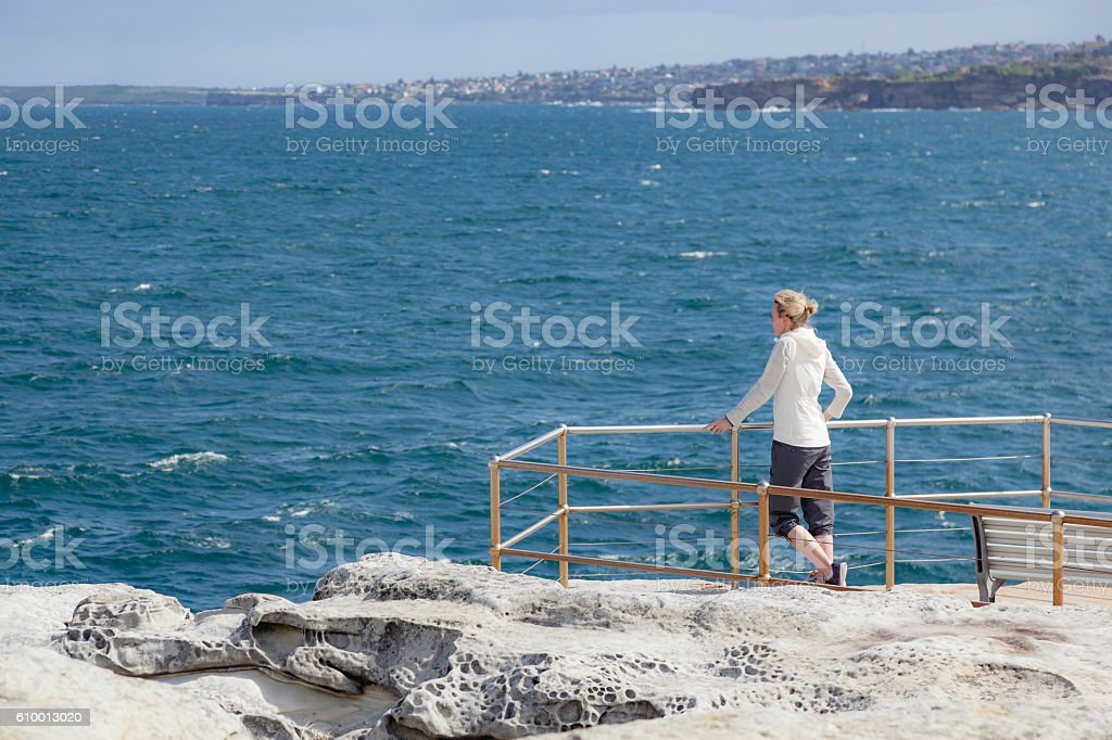Mature adult woman on cliff-top looking out to sea stock photo