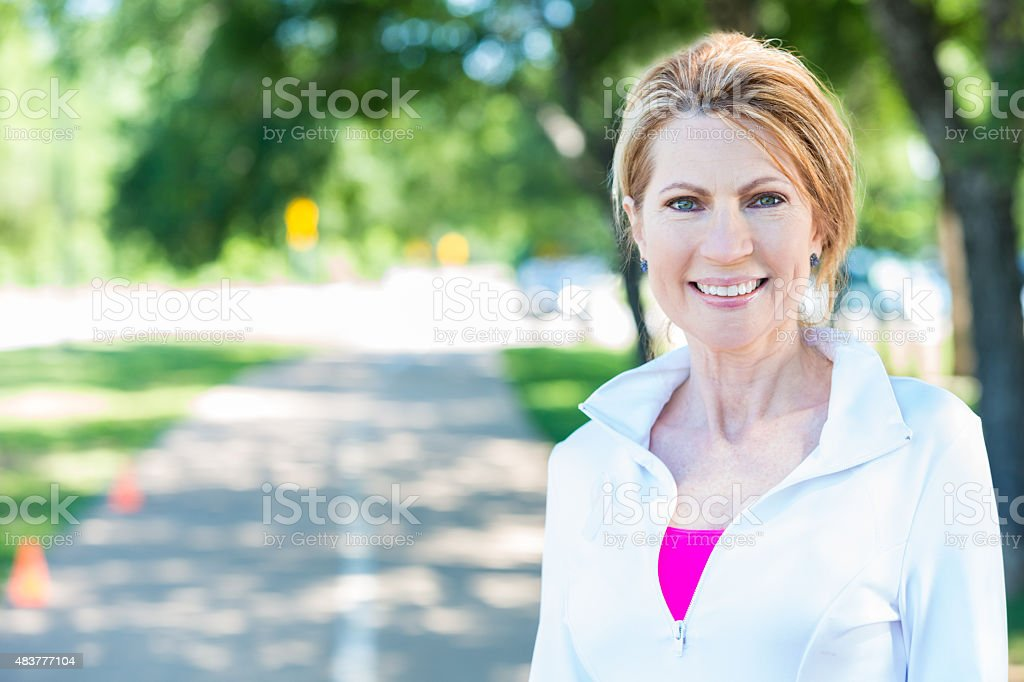 Mature adult woman smiling after running on track in park stock photo