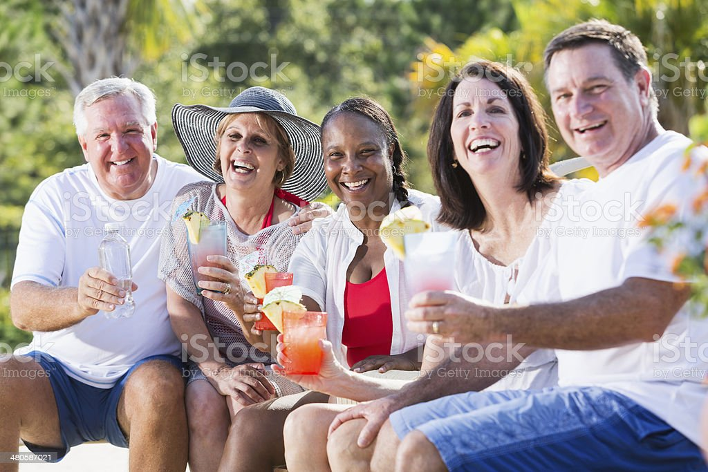 Mature adults enjoying tropical drinks stock photo