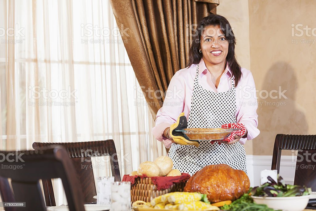 Mature African American housewife serving traditional holiday meal. stock photo