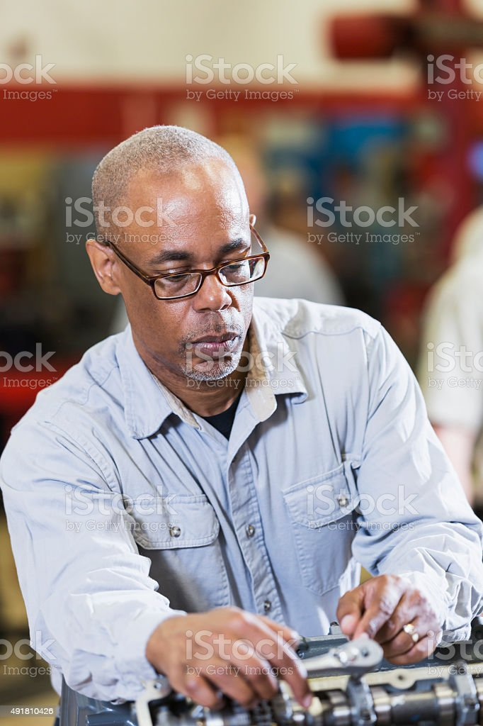 Mature African American man working on a car engine stock photo