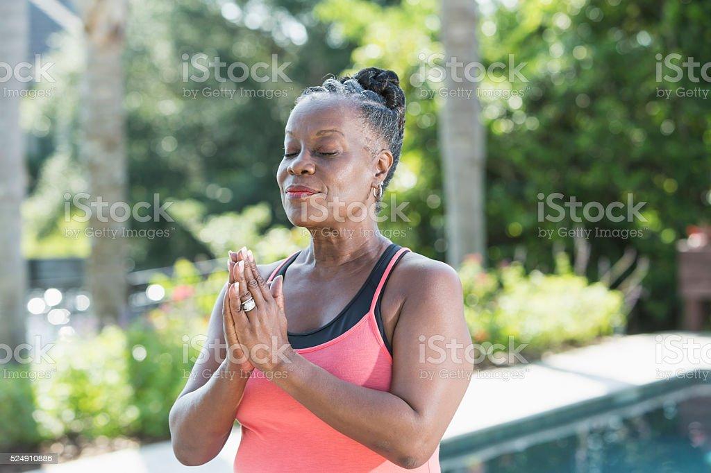 Mature African American woman meditating outdoors stock photo