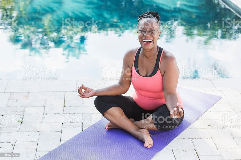 Mature African American woman on yoga mat by pool stock photo