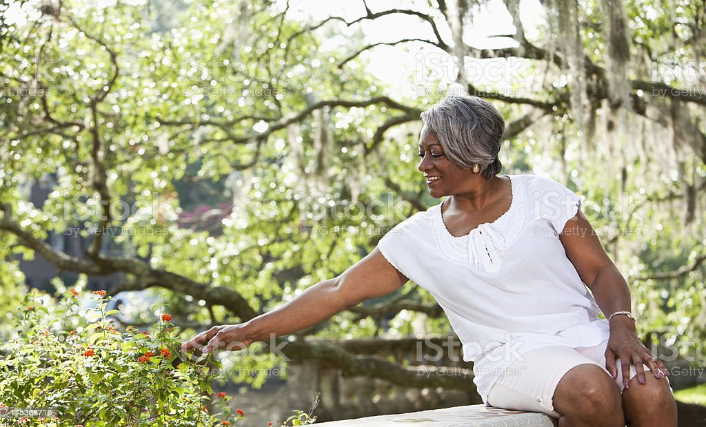 Mature African American woman sitting in park stock photo