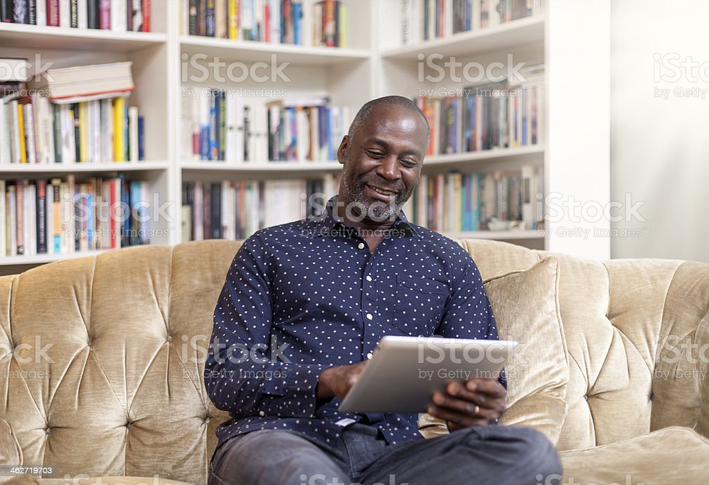 Mature african man with digital tablet smiling royalty-free stock photo