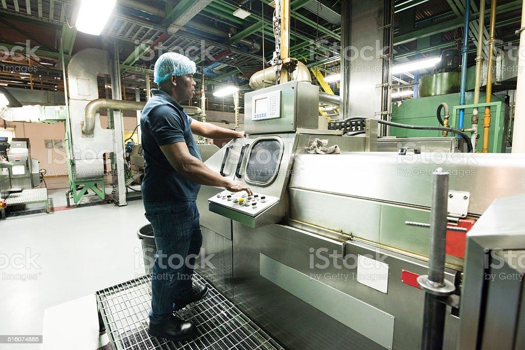 Mature African using control panel in aluminium plant stock photo