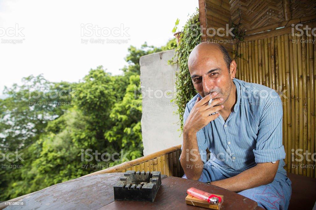 Mature and bald man smoking a cigarette stock photo