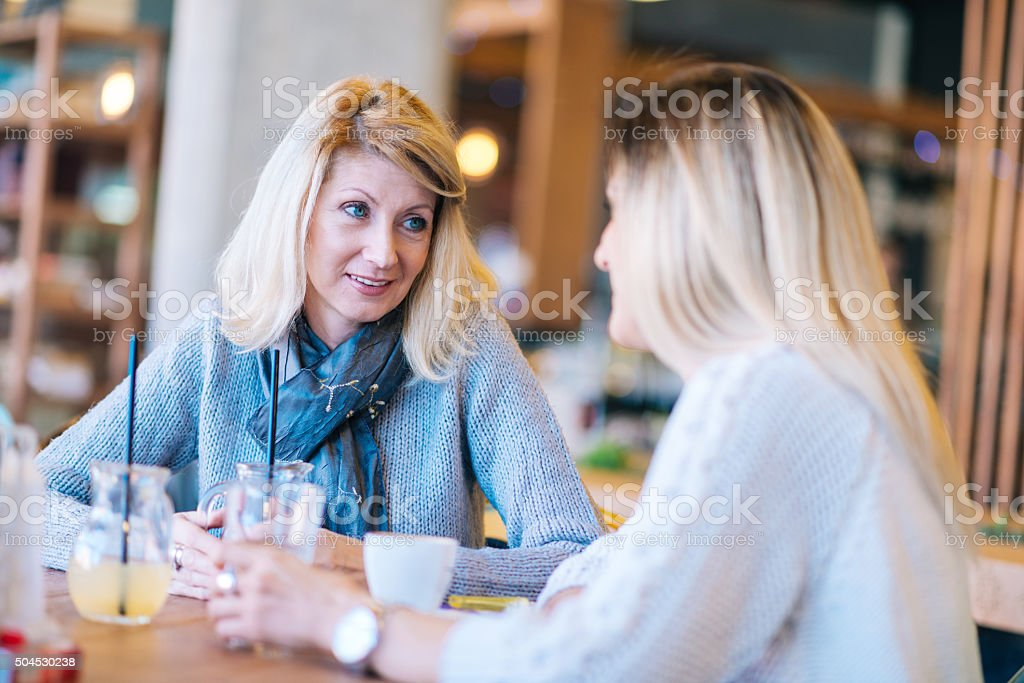 Mature and young woman having coffee time in modern cafe stock photo