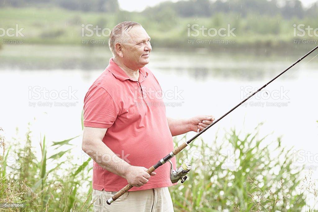 Mature angler on lake stock photo