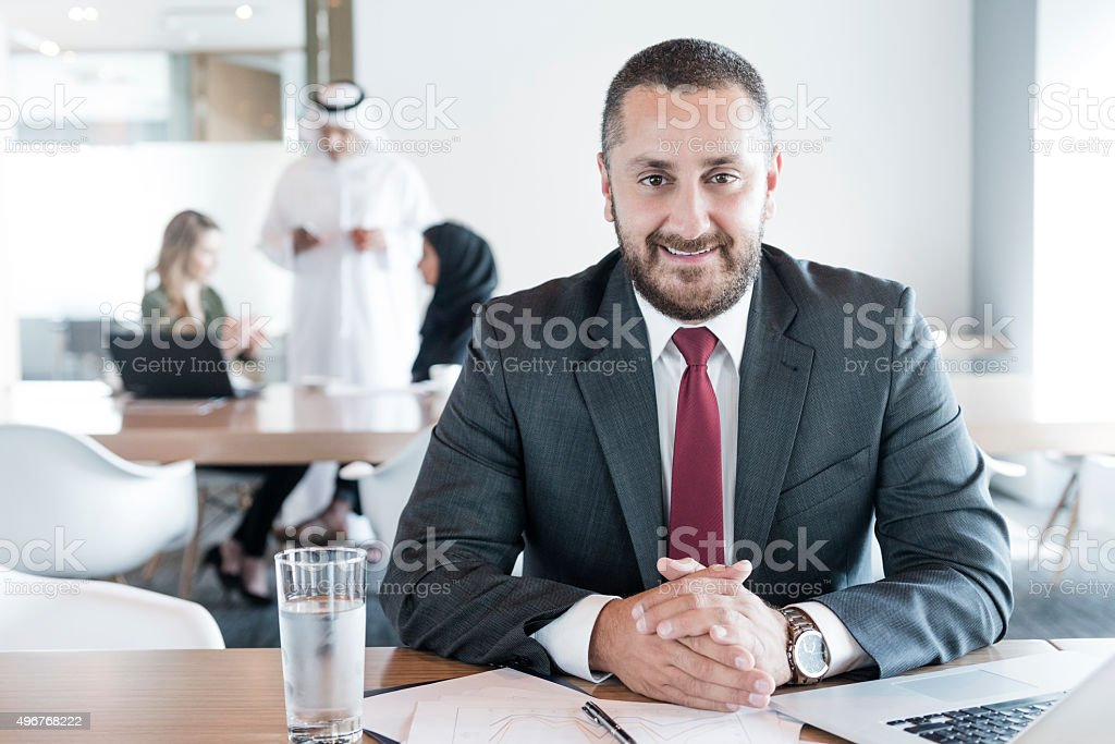 Mature Arab businessman at desk in office, portrait stock photo