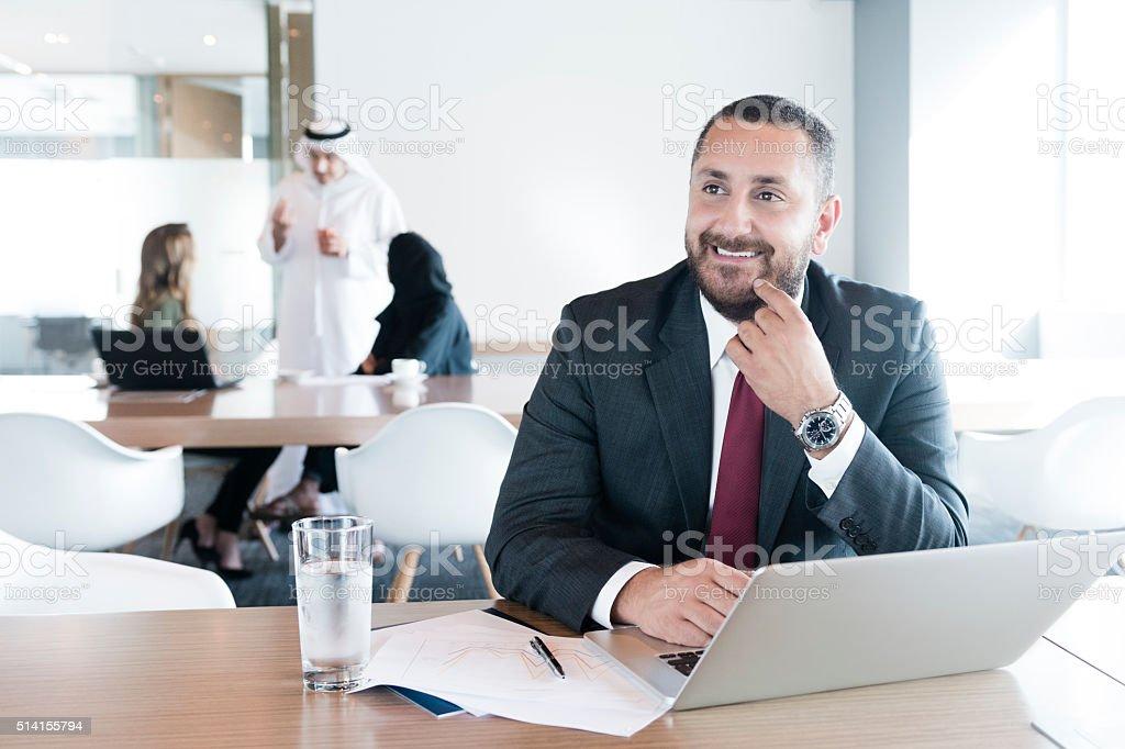 Mature Arab businessman using laptop in modern office, portrait stock photo
