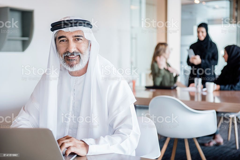 Mature Arab businessman wearing ghutra using laptop, portrait stock photo