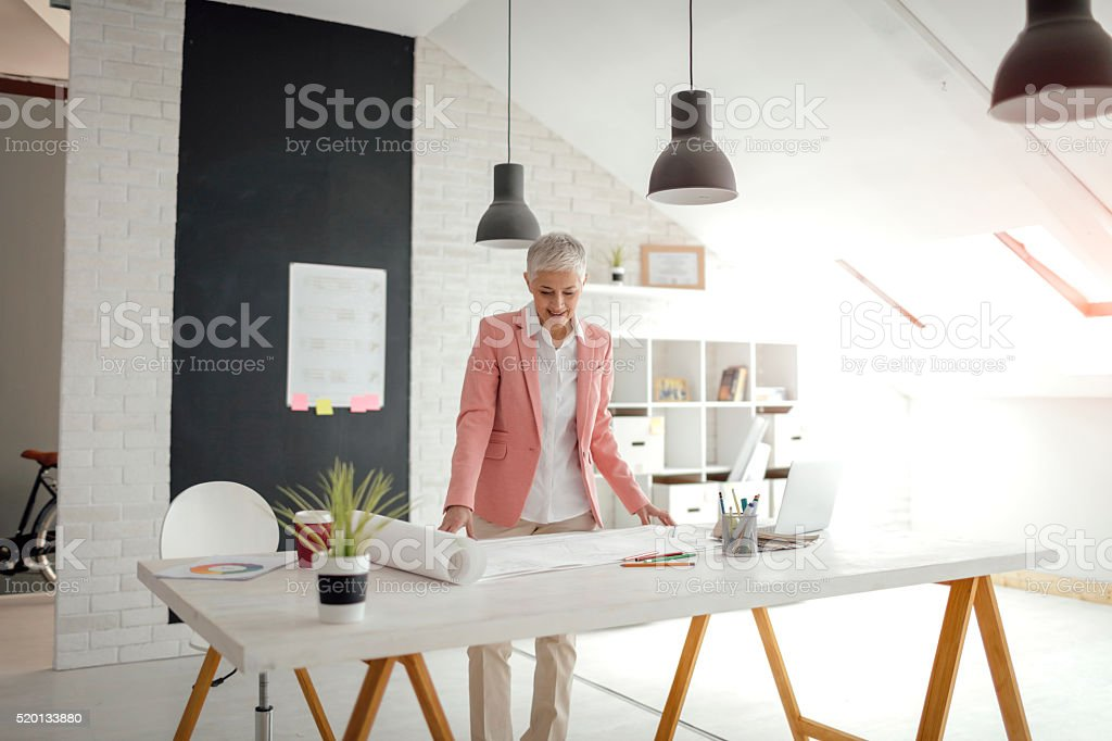 Mature Architect working in her office. stock photo