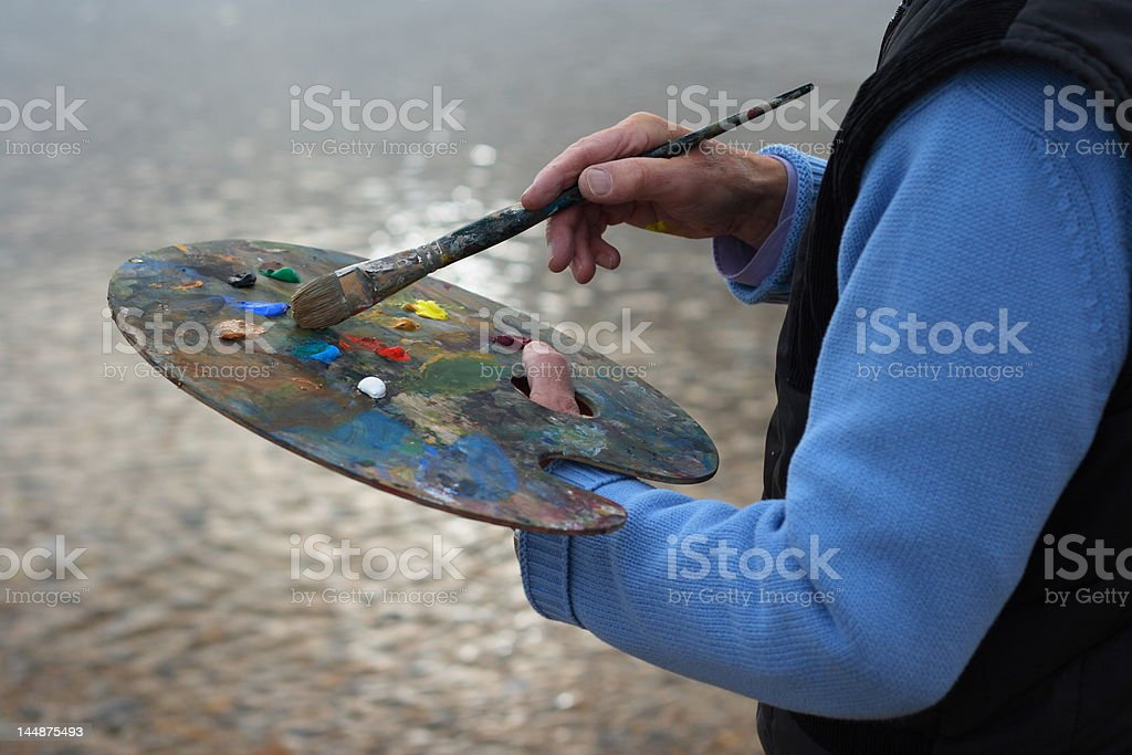 Mature artist painting by the sea royalty-free stock photo