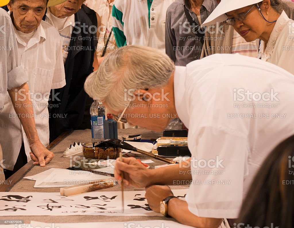 Mature artist painting chinese calligraphy royalty-free stock photo