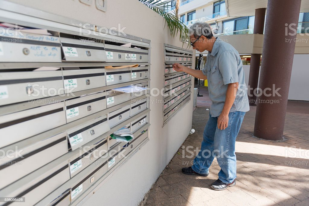 Mature Asian Man Checking Mail Box stock photo