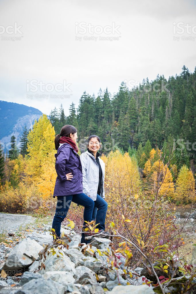 Mature Asian Mother and Teenage Daughter Hiking in the Wilderness stock photo