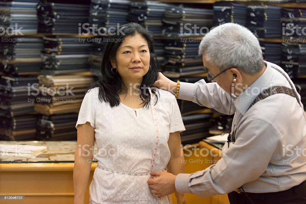 Mature Asian Woman Being Measured by Tailor for Handmade Suit stock photo