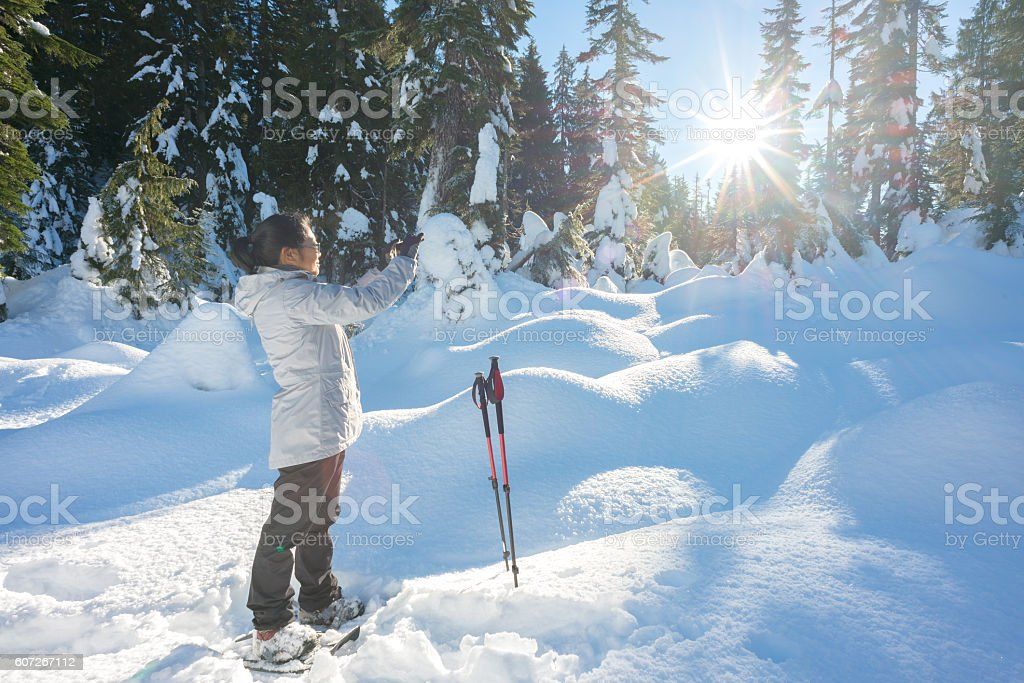 Mature Asian Woman Taking Cellphone Photo While Hiking with Snowshoes stock photo
