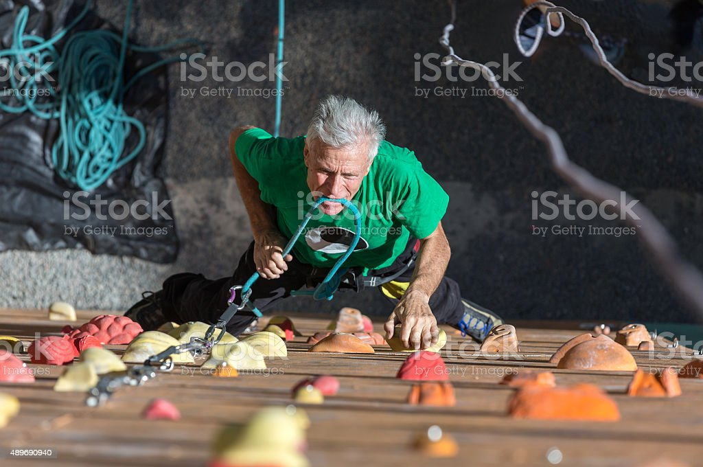 Mature Athlete Fixing Rope into Belaying Device stock photo