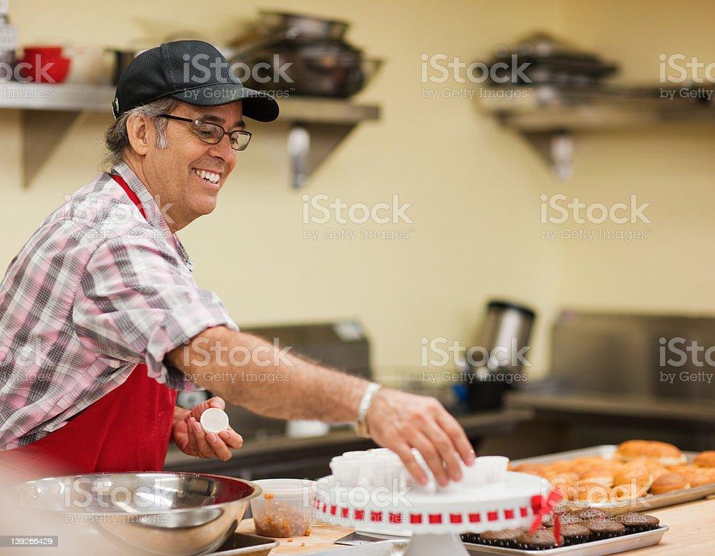Mature baker preparing food in kitchen stock photo