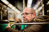 Mature balding man on public transport