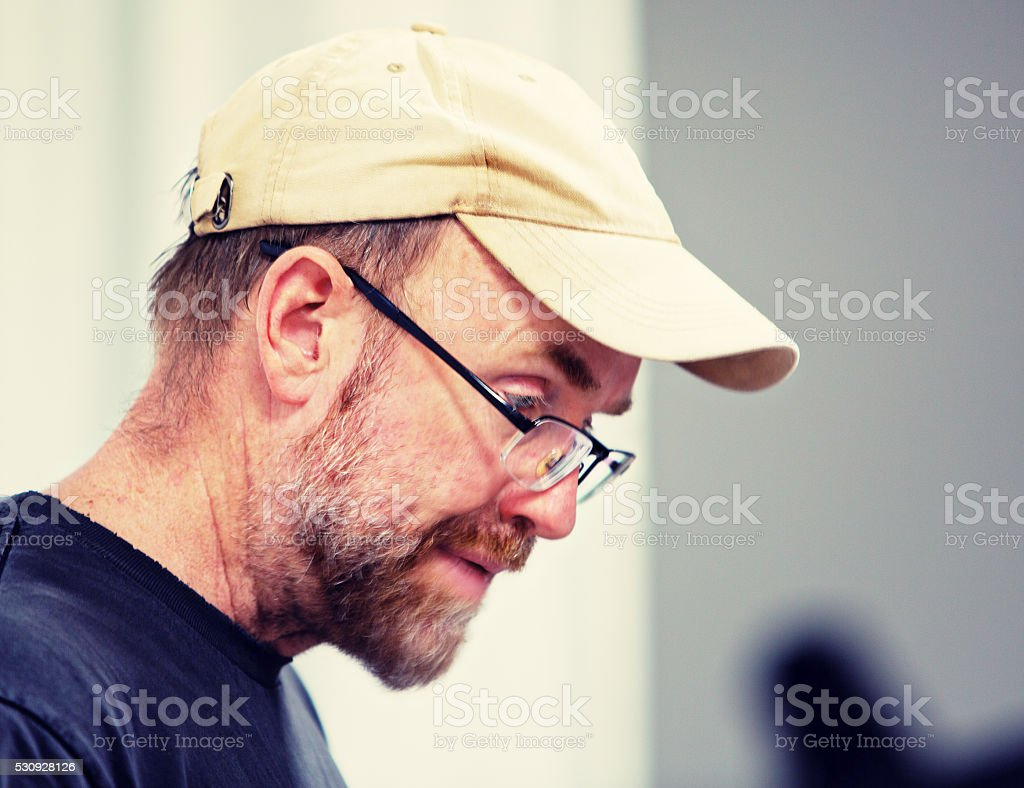 Mature, bearded man in cap looks down, frowning, concerned stock photo