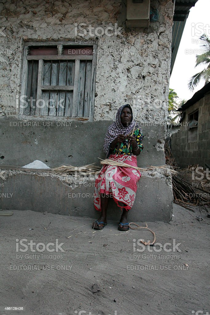 Mature black African woman sits near stone house, Zanzibar, Tanzania. stock photo
