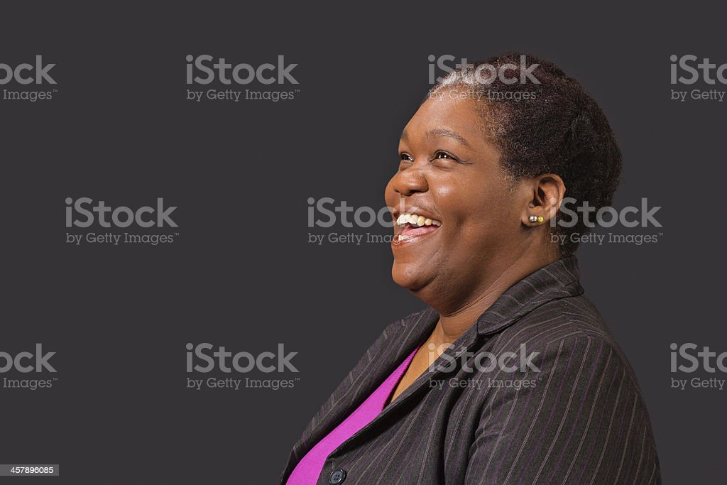 Mature black woman in suit looking up and laughing. Dark gray...