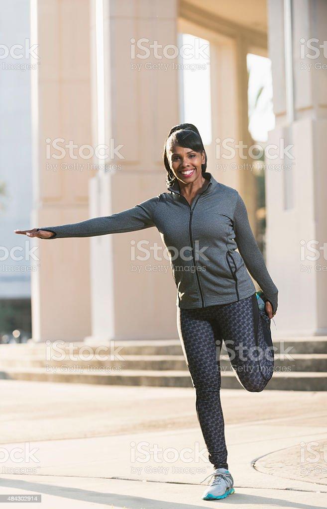 Mature black woman stretching her leg stock photo