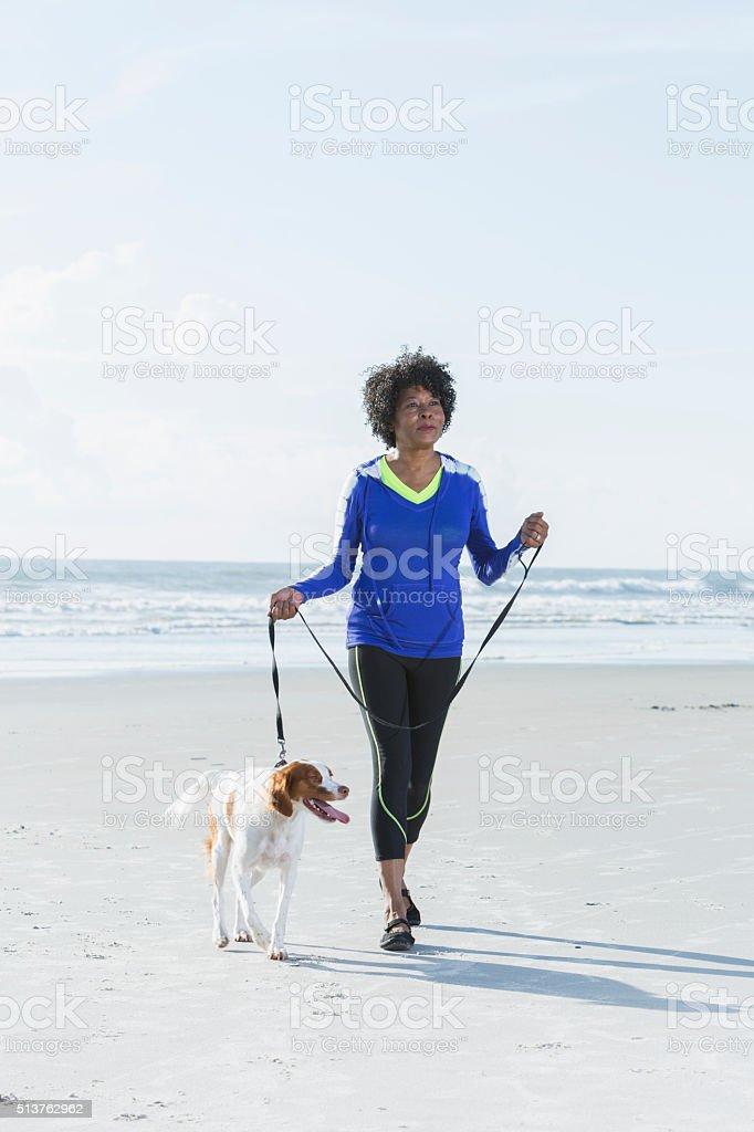 Mature black woman walking dog on beach stock photo