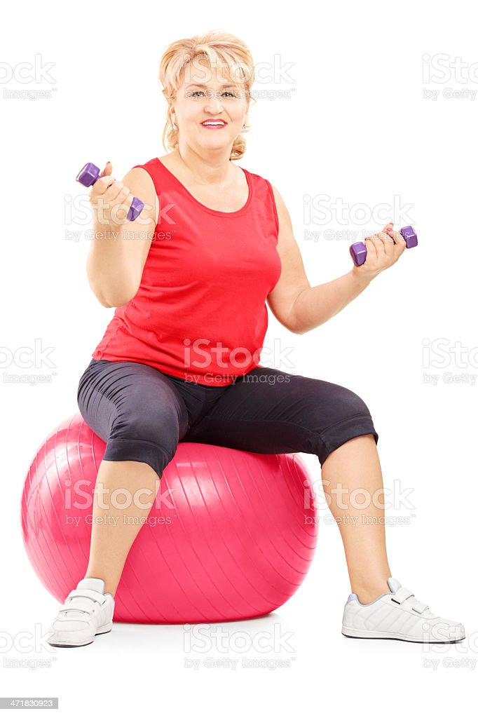 Mature blond female sitting on ball and exercising with dumbbells stock photo