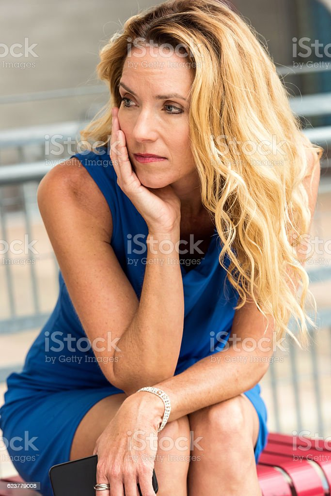 Mature blond woman waiting for the bus stock photo