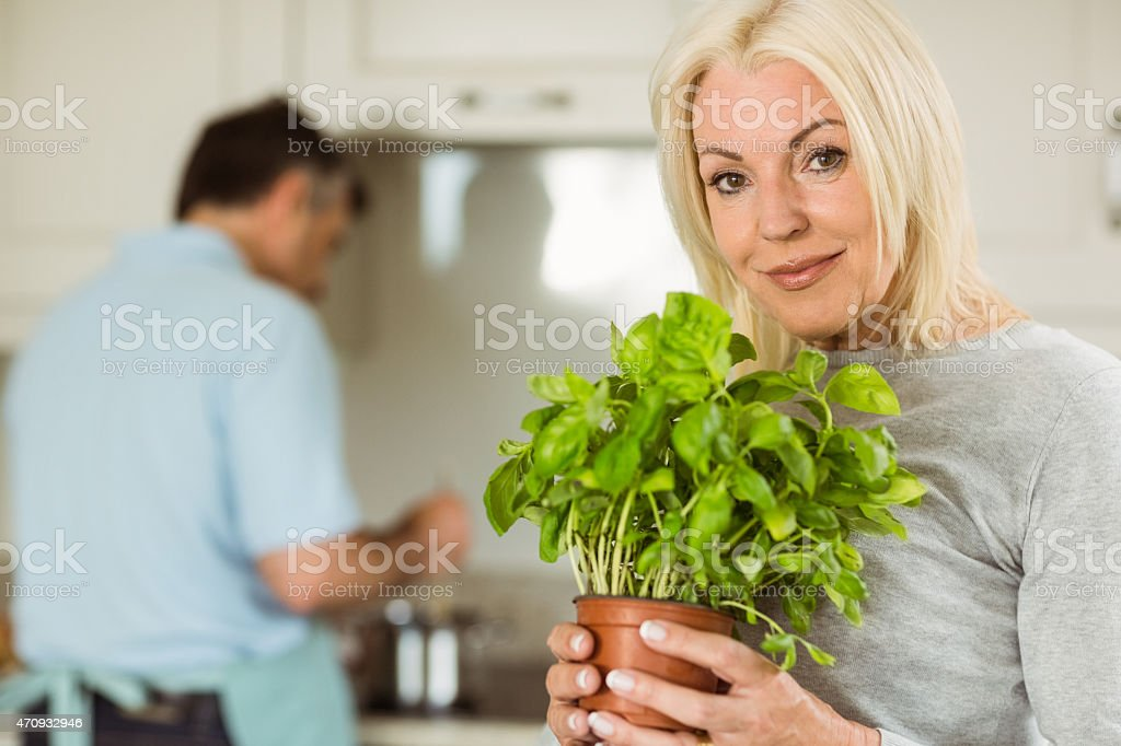 Mature blonde smiling at camera holding basil plant stock photo