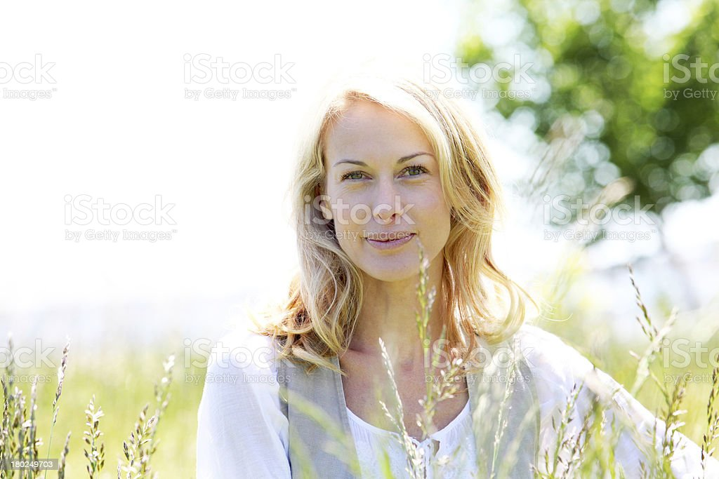 Mature blonde woman sitting in meadow on sunny day royalty-free stock photo