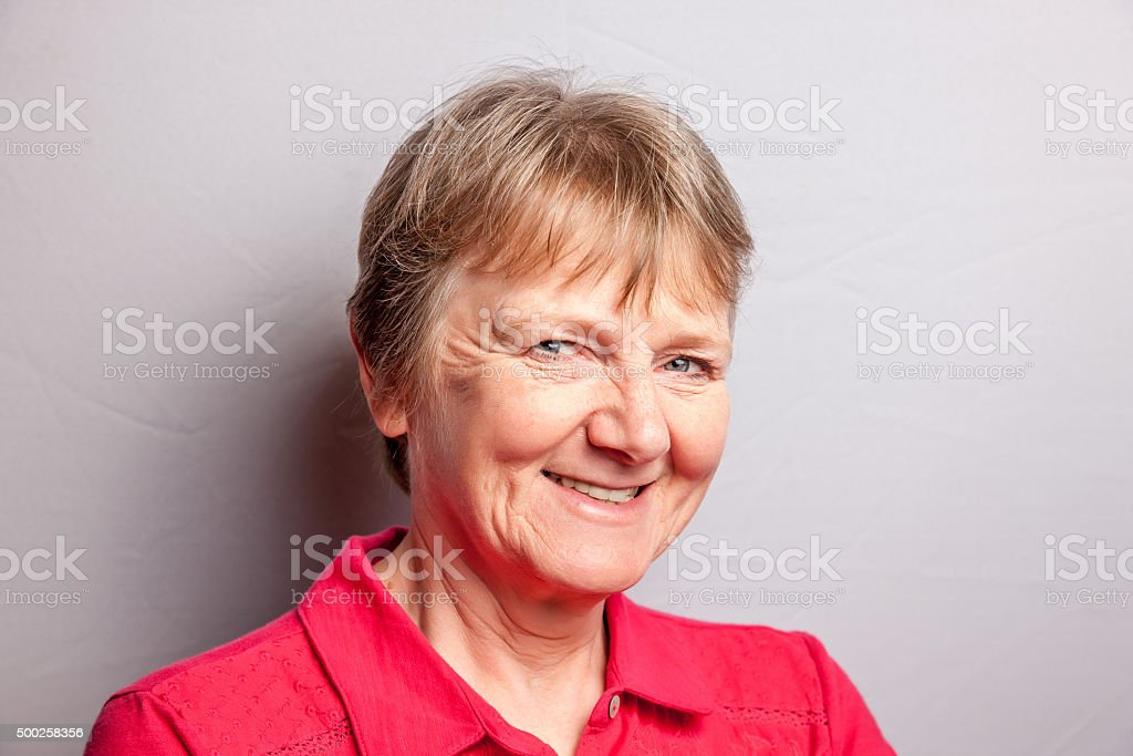 Mature blonde woman smiling headshot stock photo